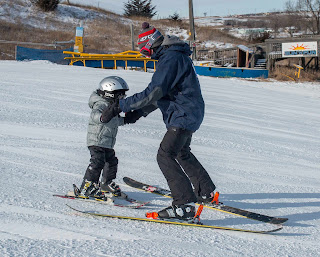 a ski instructor helps a young child gain their balance on skis at Great Bear Ski Valley in Sioux Falls, South Dakota