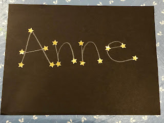"""Anne"" written in white crayon on black background with yellow stars on the points of the letters"
