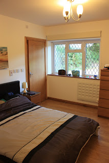 Picture of our bedroom in the apartment, with wooden floor, double bed (quite low) and plenty of space.