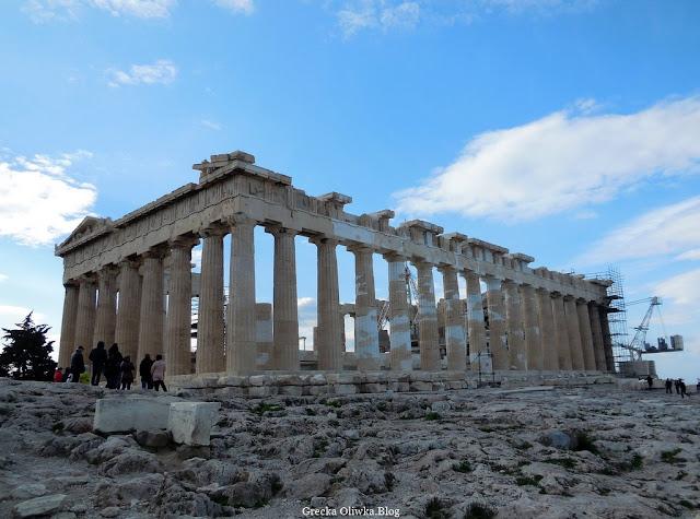 Partenon, Ateny Grecja , skaliste podłoże, zabytkowe wysokie kolumny Partenonu, na błękitnym niebie lekkie białe chmury
