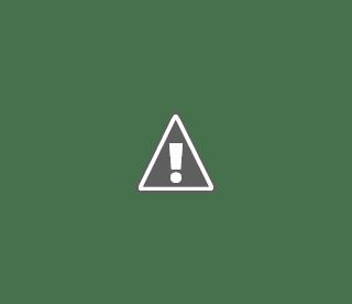 Fotografía de un niño con diversidad funcional en una biblioteca con otra niña