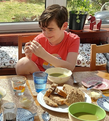 child eating bread with soup at dining table