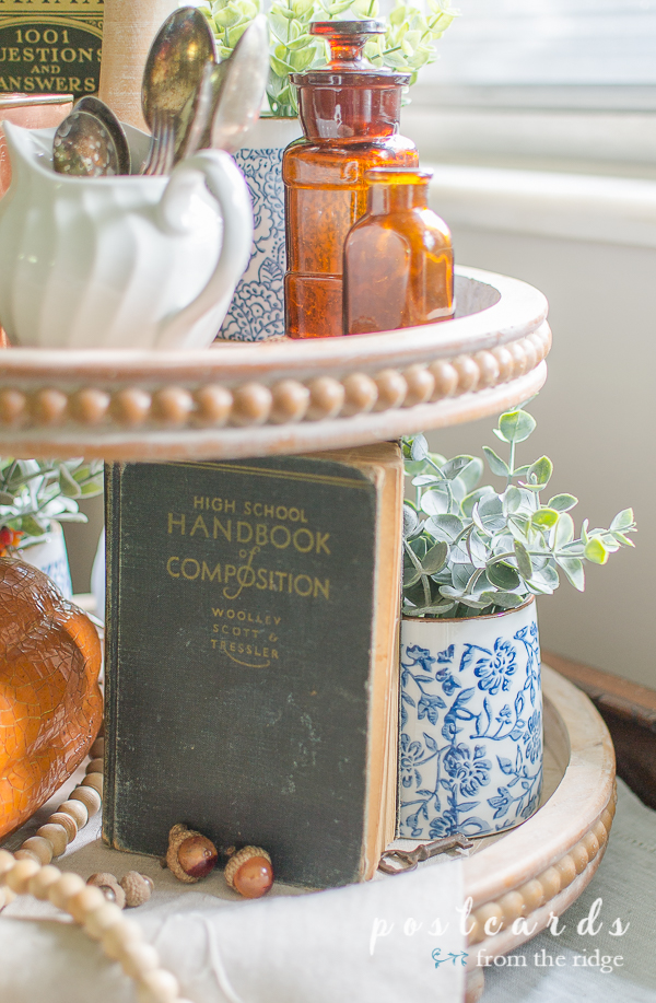 old high school composition handbook and fall decor on wood tiered tray