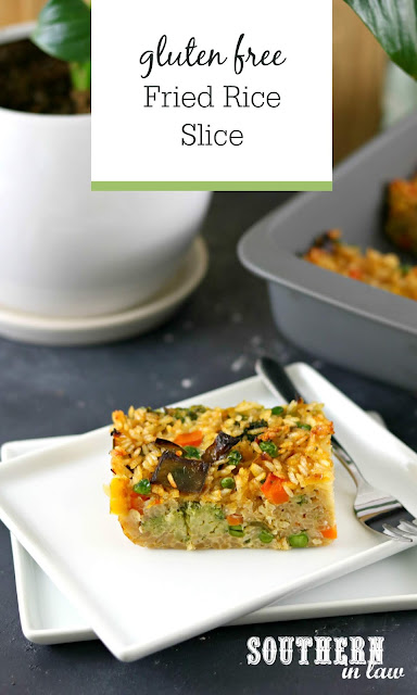 Easy Gluten Free Fried Rice Slice Recipe - slice of baked fried rice on white rectangular plate in front of grey baking dish and plant in white pot with peace lily