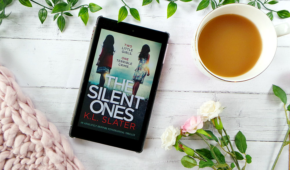 A kindle fire is on a table with some leaves, a pink chunky knit blanket and a cup of tea. The kindle shows the cover of The silent ones. The cover shows 2 young girls stood back to back