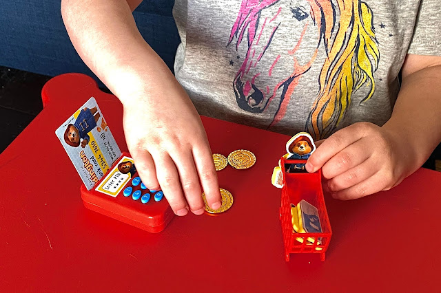 Close up of the toys with the first issue of the paddington bear magazine including a plastic chip and pin machine, mini shopping trolley, foam pieces and a pretend cash card