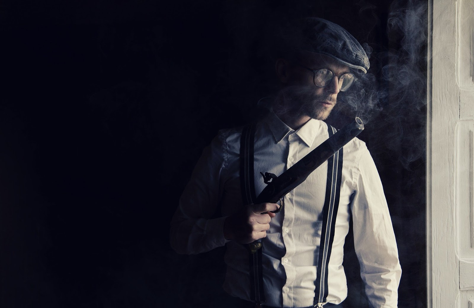 Mobster looking out window while carrying smoking gun to illustrate blog post about mob warfare