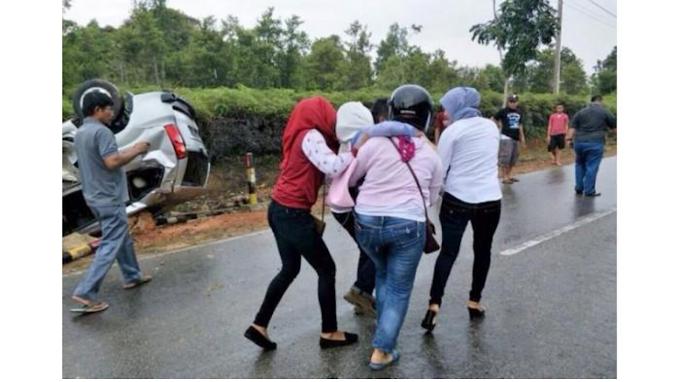 Menolong korban kecelakaan di jalan raya
