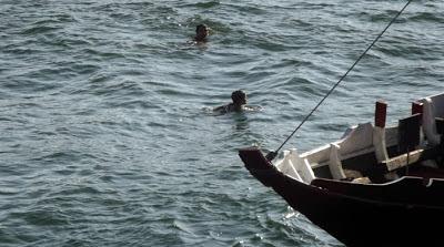 meninos nadando no rio Douro próximos de um barco