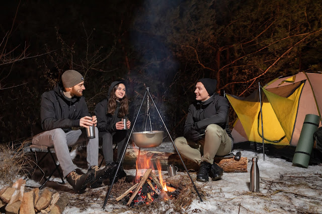 A group of people sat around a campfire wearing black Gamma Jackets