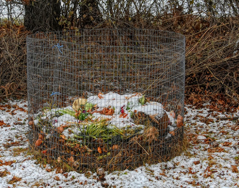 chain fence surrounding compost in winter snow