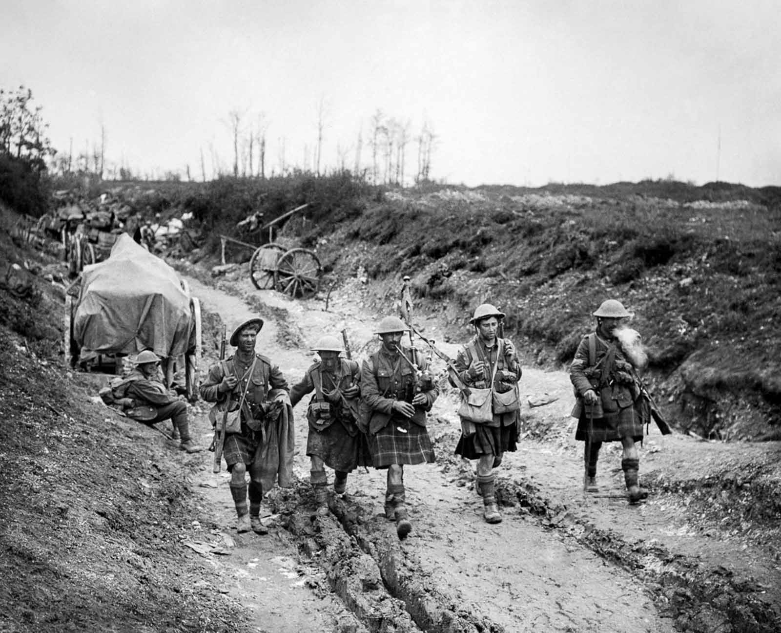 A piper of the 7th Seaforth Highlanders leads four men of the 26th Brigade back from the trenches after the attack on Longueval. July 14, 1916.