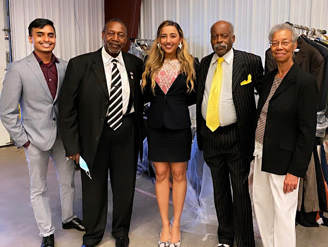 (Left to right) ENS Anuj Kambalyal (USU medical student), Melvin Woodard, Zoya Mahajan (USU medical student & volunteer), Prince Rawlings (founder of the Suit Drive for Veterans), and a supporter stand in the Clinton, MD warehouse space.