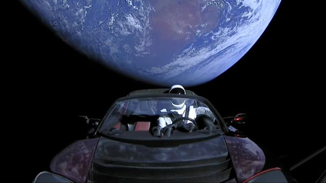 A view of Starman inside the Tesla Roaster with Earth falling away in the background. Photo Credit: SpaceX Webcast