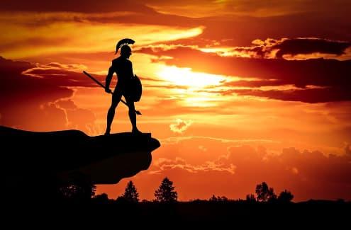 A imagem mostra a sombra de um soldado medieval sobre um monte observando o horizonte sob um por do sol avermelhado.