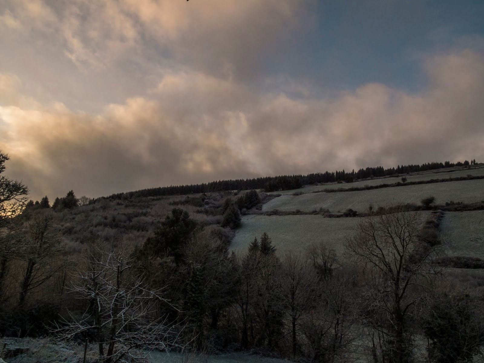 Snow covered landscape of a hillside in North Cork at sunset.
