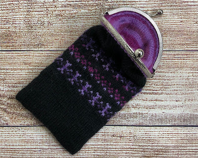 Coin purse knitted with DROPS Fabel Black and Candy Print showing inside liner