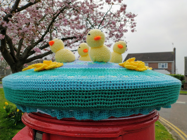 Knitted postbox cover with Easter chicks and spring daffodils