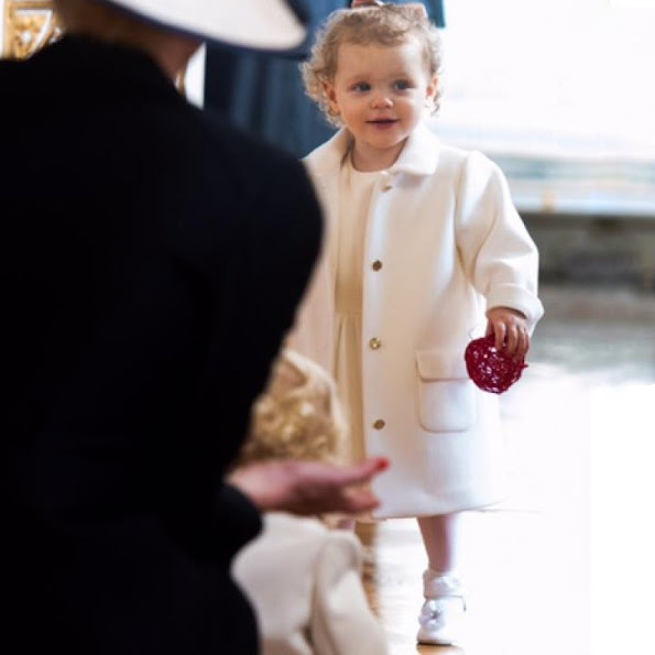 Princess Gabriella donned a satin dress with a bodice and skirt in multilayered tulle, completed by a satin sash tied at the waist with a bow, a wool shrug and a coordinated cashmere coat with gold satin buttons.