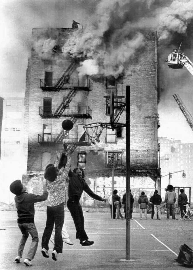 Young boys ignore a 1975 apartment building fire while playing basketball in front of the blaze.  Baskets and Ladders. marchmatron.com