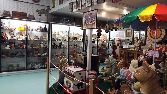 The American Museum of the House Cat display cases filled with cat-related art and other items. Carousel Cats are on the right.