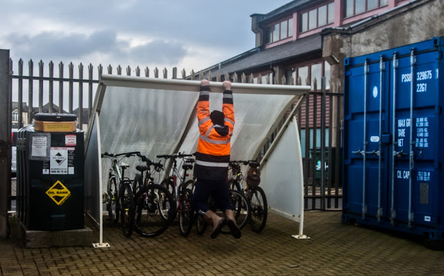 Photo of one of the marina staff holding down the roof of the bike shed