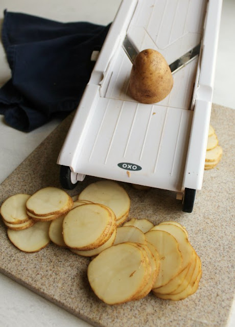 potato being sliced on OXO mandoline slicer