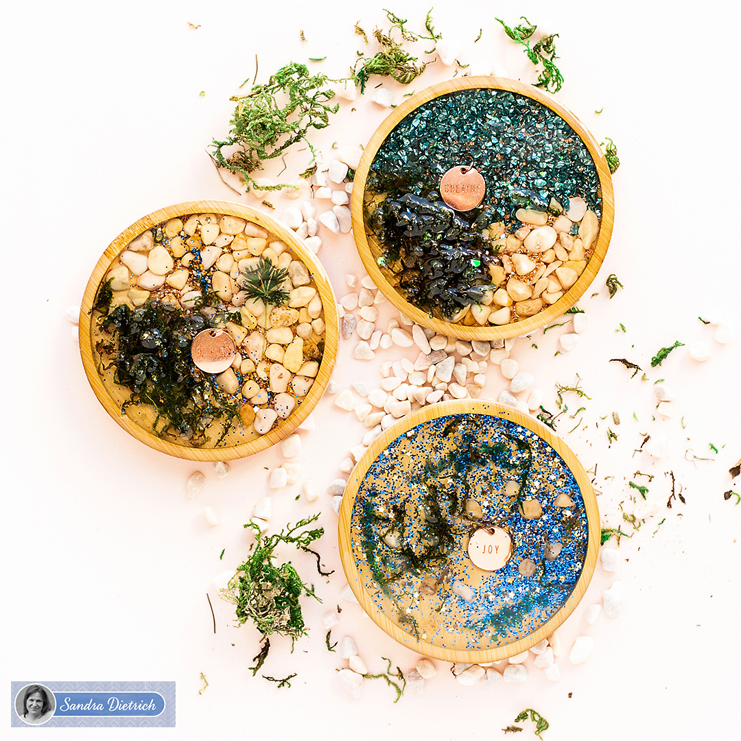 Handmade wood coasters with charms, white pebble stones, and green moss for shiny table decoration