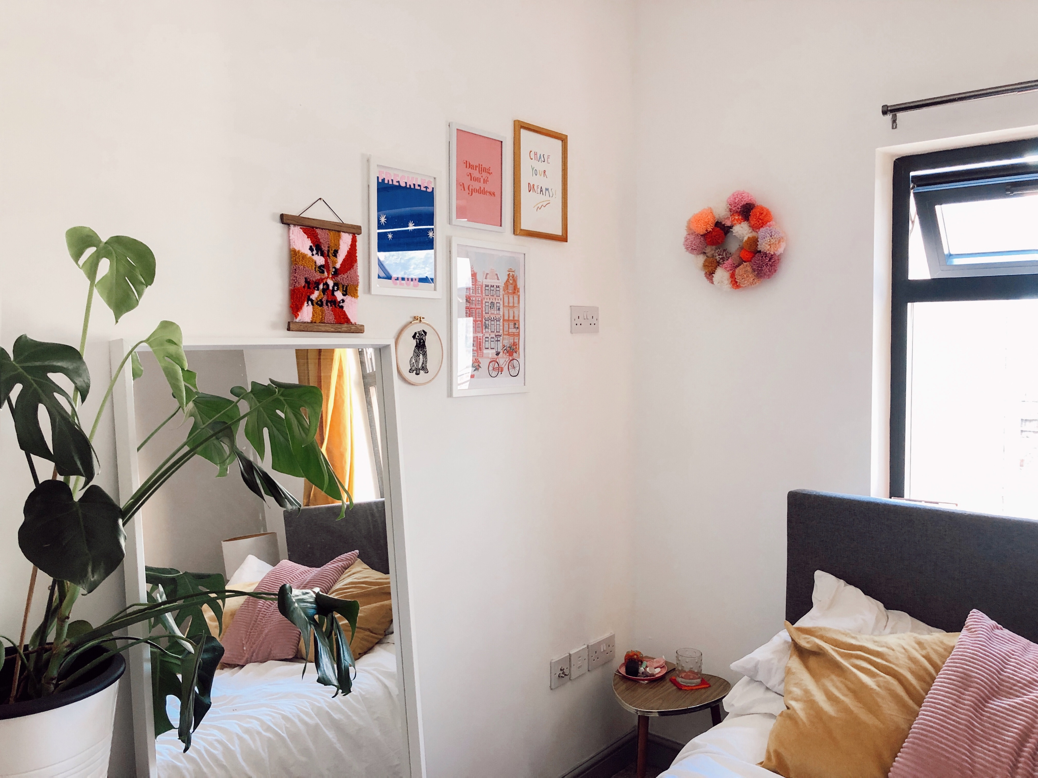 photograph of bedroom with white walls, monstera cheese plant, large mirror, gallery wall of orange, blue and pink art