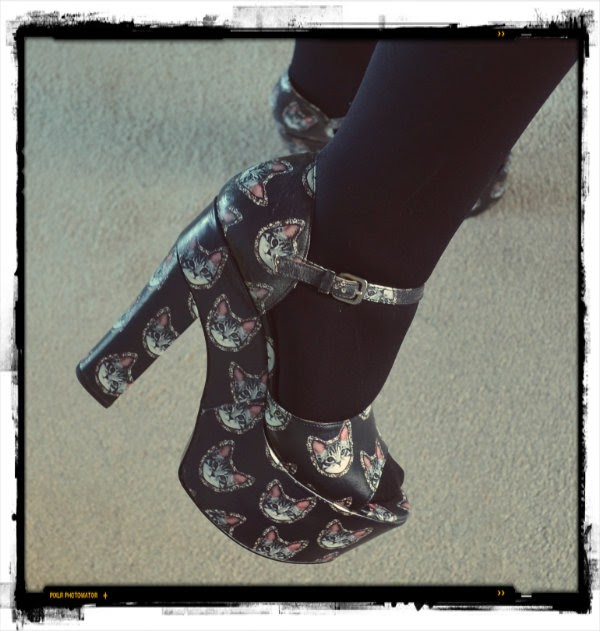 wearing large black platform sandals with cat face print and black tights