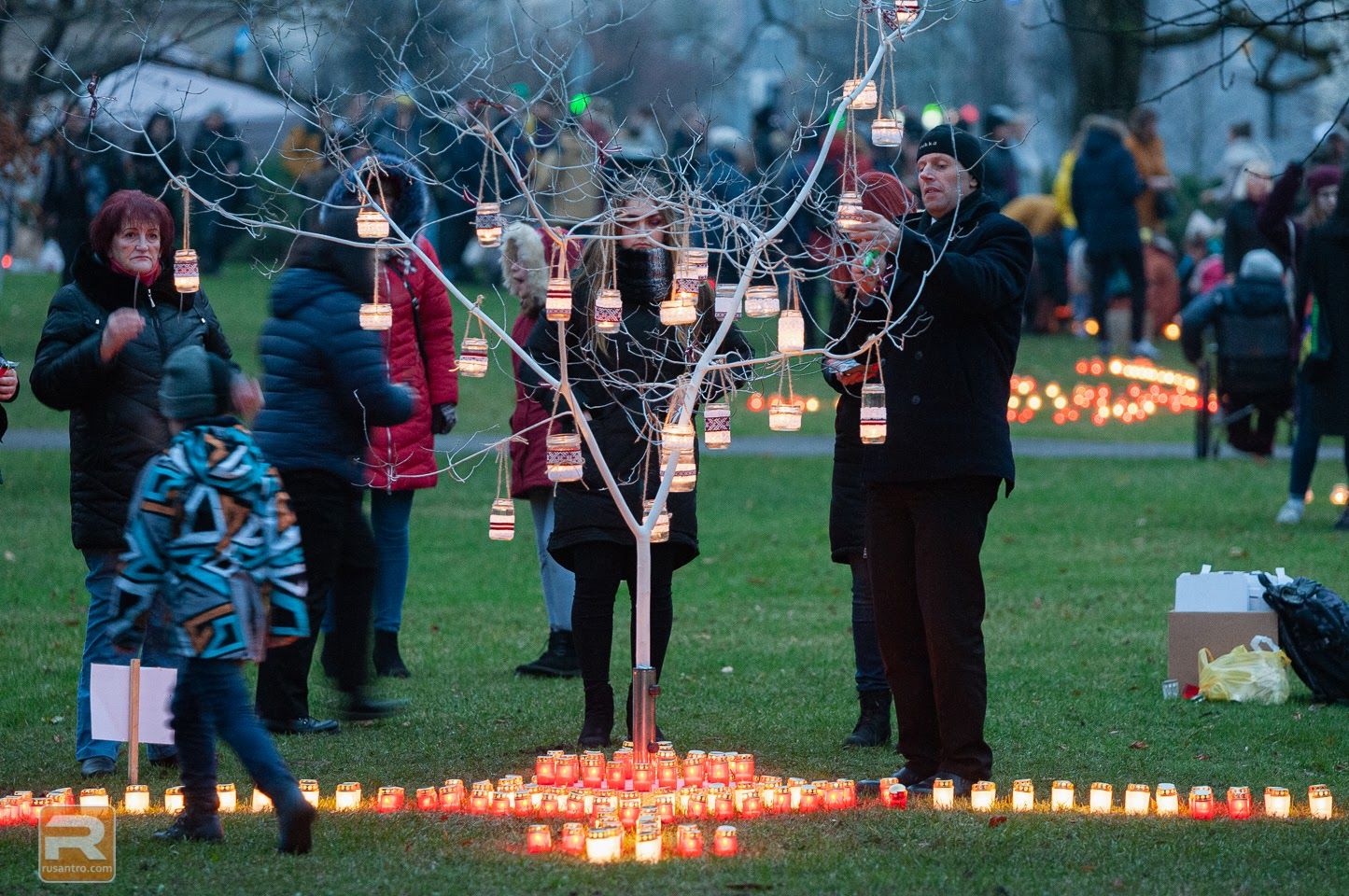 Vīrietis iekar kokā degošo svecīti