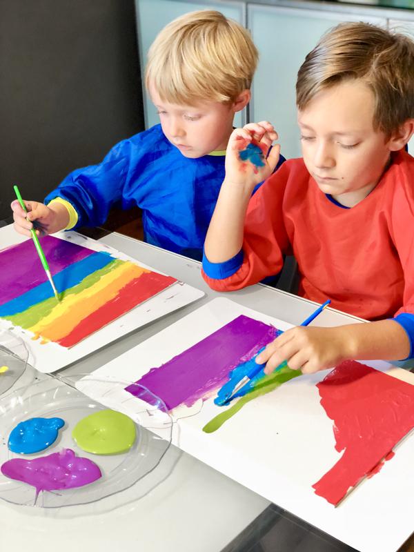 Kids painting rainbow stripes on canvas