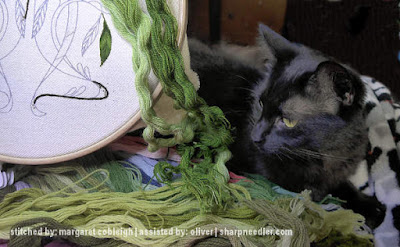 Black cat helping with crewel embroidery