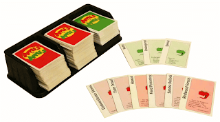 A plastic tray with spaces for three stacks of cards, capable of holding about a hundred or so cards each. Two of these are filled with cards that have red backs and the 'Apples to Apples' logo, which is the game's name on a yellow circle. The third compartment has a similar stack of cards, except the backs are green instead of red. Spread nearby are six of the red cards, face up, showing the red apple character and the card's titles: Convenience Stores, Time Travel, Hawaii, Food Poisoning, Sandra Bullock, and Redwood Forests. Also nearby is a spread of three green cards, which look similar apart from being green. The titles are: Nutty, Endangered, and Special.