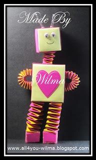 Een roze robot gemaakt van muizentrappetjes, vouwblaadjes en wiebeloogjes. A pink robot made of accordion papercrafts, thin paper and wiggle eyes.