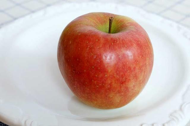 Ein roter Apfel auf einem weißen Teller