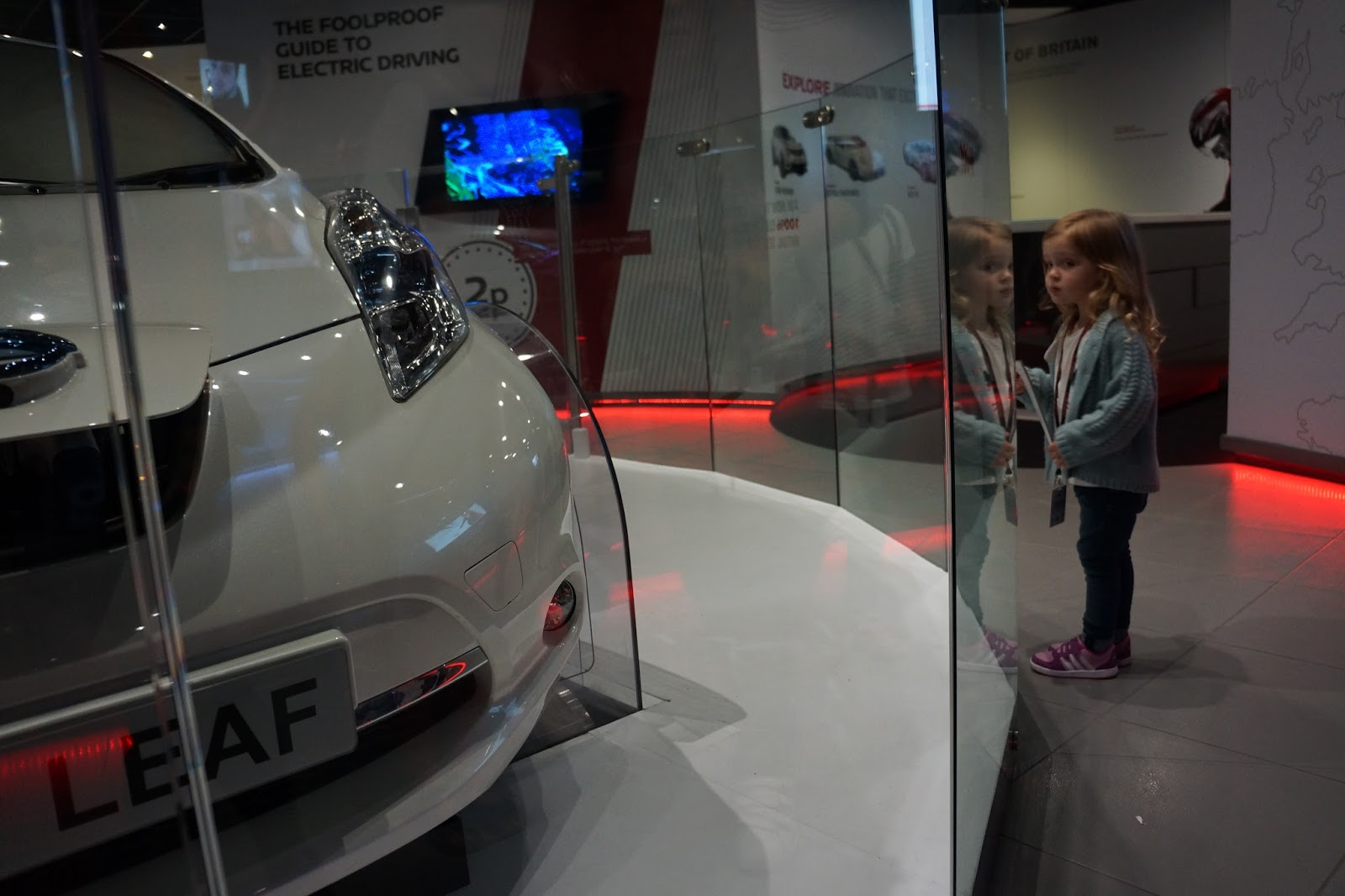 toddler looking at a car at nissan innovation station at the o2
