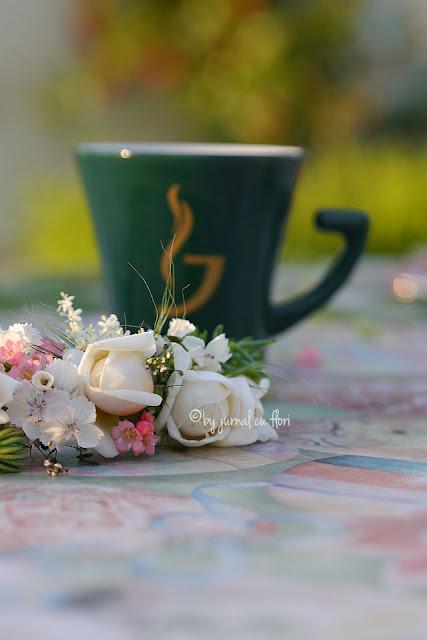 masa cu ceasca de cafea si flori superbe