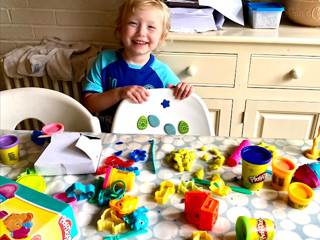 a child standing behind a table with a mess of play-doh items on it