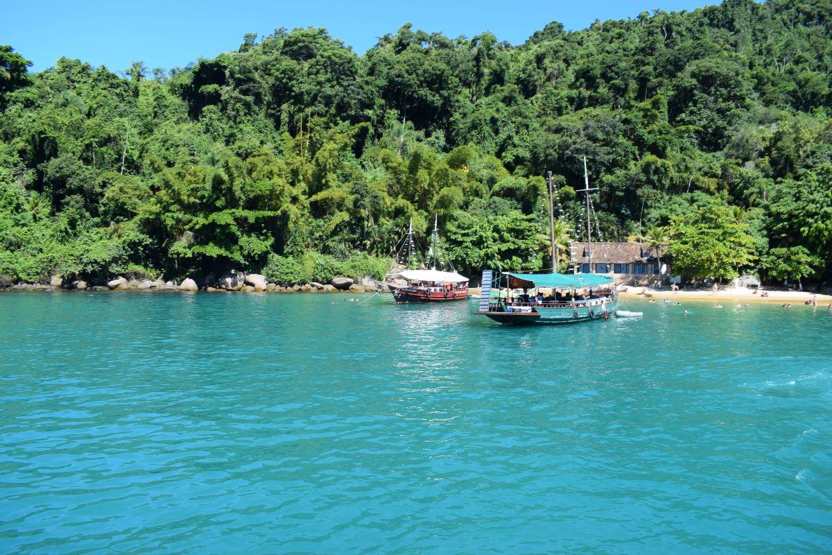 praia com escunas ancoradas em ilha pequena em mar aberto de águas esverdeadas