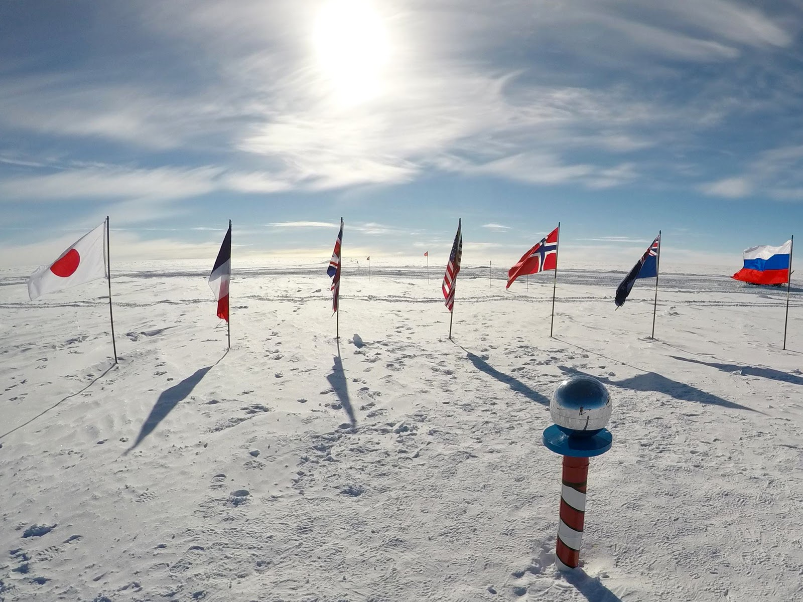 The South Pole marker surrounded by the flags of different nations