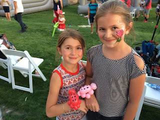 Two young girls posing with their faces painted and balloon ladybugs