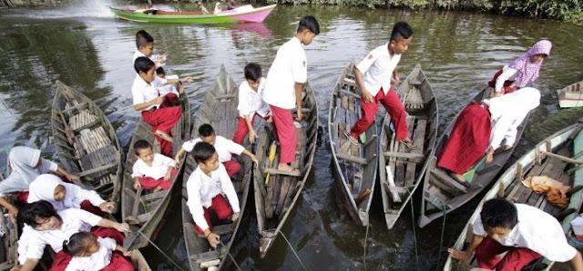 Siswa Menyeberang Sungai dngan Sampan