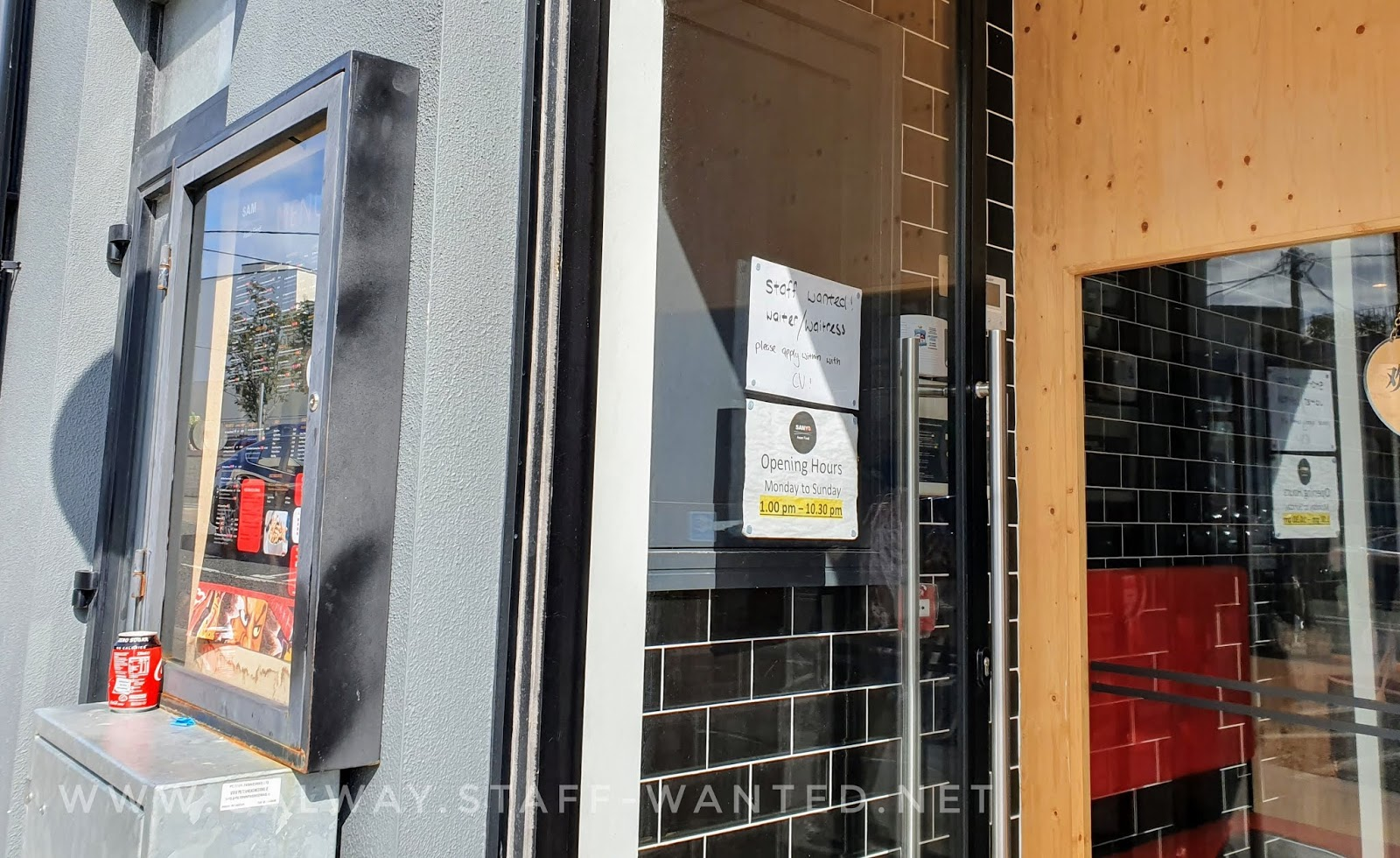 front door showing opening hours and closing time as well as staff-wanted sign.