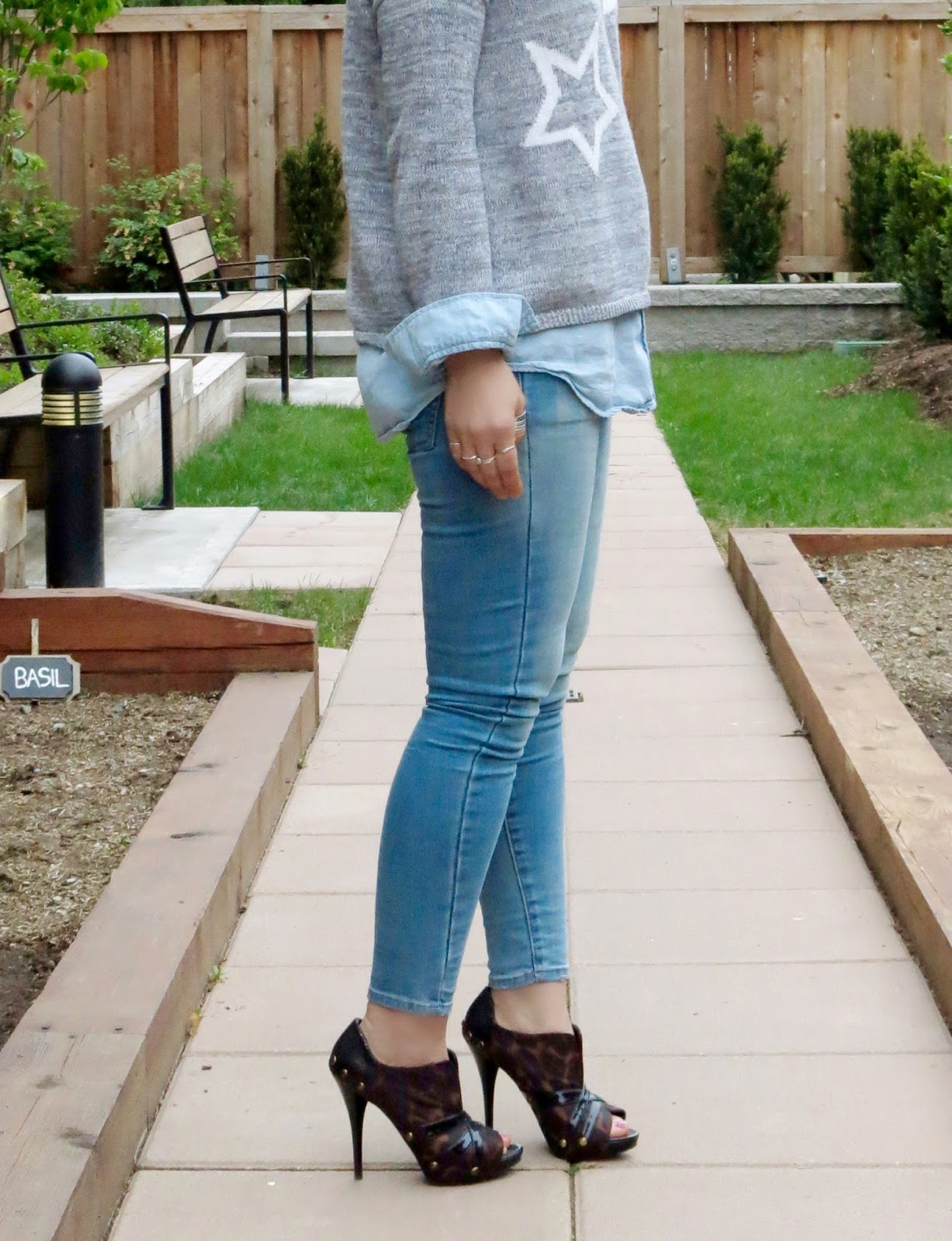 chambray shirt layered under a star-patterned sweater, skinny jeans, and leopard heels