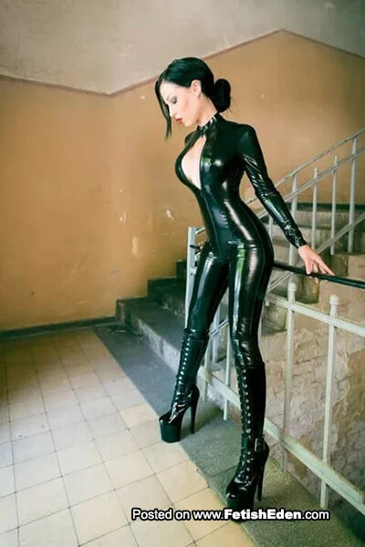 Amy Grey with green hair wearing green latex catsuit