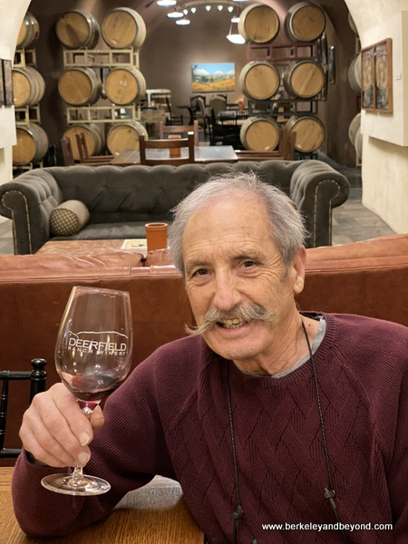winery owner Robert Rex holding a glass of 2012 Syrah Cuvee in cave tasting room at Deerfield Ranch Winery in Kenwood, California