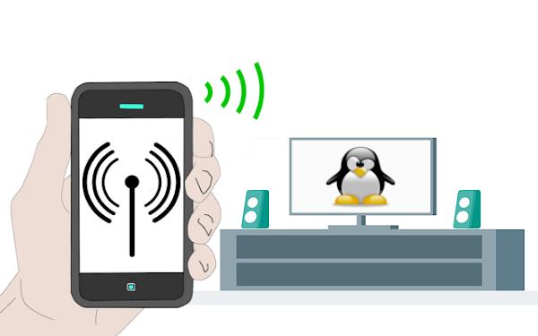 Uma mão segurando smartphone e uma mesa com um computador