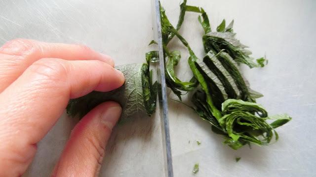ご飯を炊いている間に青じそをせん切りに切ります。 軽く水洗いして水けをきった青じその葉元の茎部分を切り落とし、クルクル手前から巻き、端からせん切りに切っていきます。幅は1㎜を目安に。
