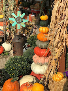 a pile of pumpkins sits next to fall decorations at Solsma's Pumpkin Patch